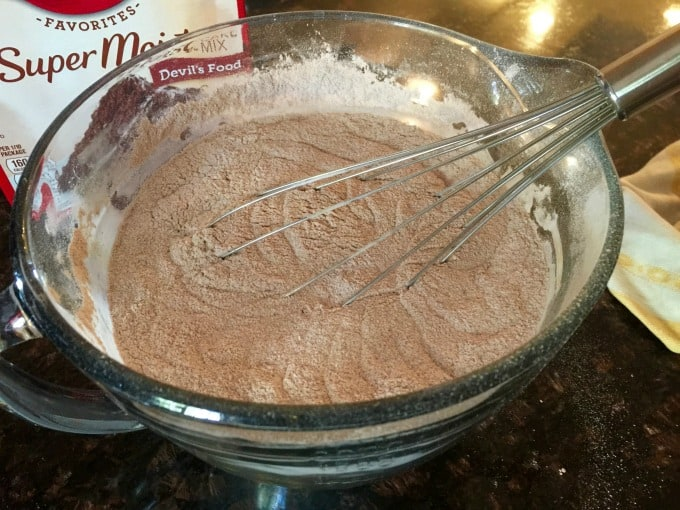 Whisking together the cake mixes in a large clear bowl with a balloon whisk