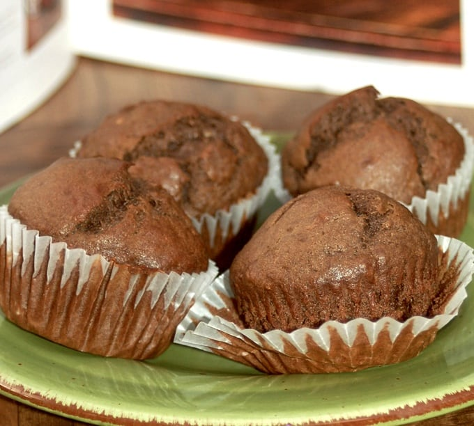 Four chocolate banana muffins on green ceramic plate.