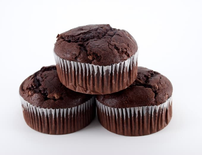 1 giant chocolate chocolate chip muffin stacked on 2 giant double chocolate muffins