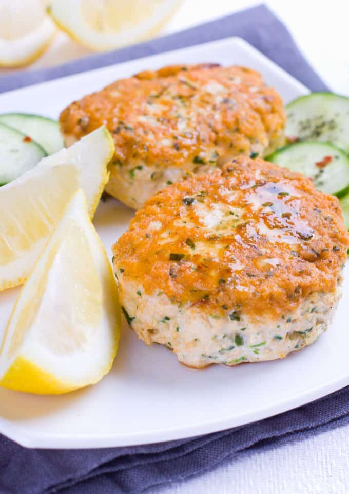 Two Salmon Patties on a white plate with lemon wedges and sliced cucumber