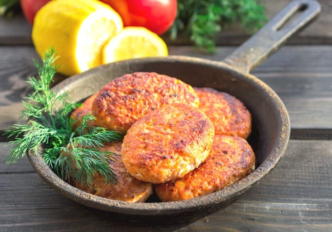 Salmon Cakes in Cast Iron Skillet with Lemon and Tomatoes on Dark Wood Table