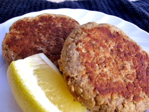 Two Cooked Salmon Cakes on White Plate with Lemon Wedge