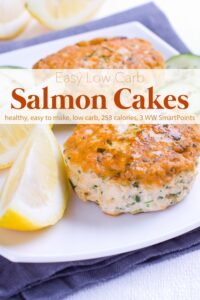 Two salmon cakes with lemon wedges on white dinner plate.