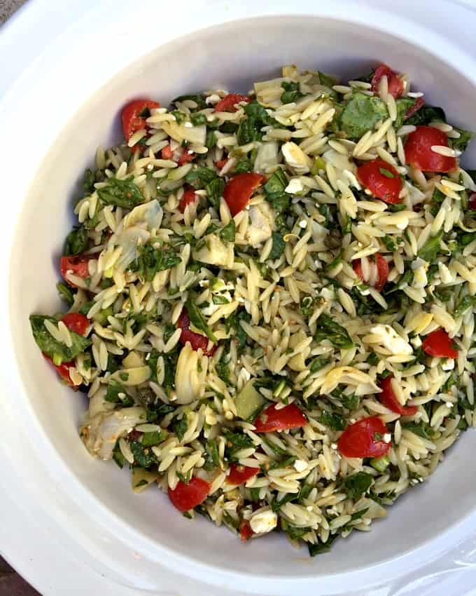 Orzo Pasta Salad with Tomatoes, Spinach and Artichoke Hearts in white serving bowl