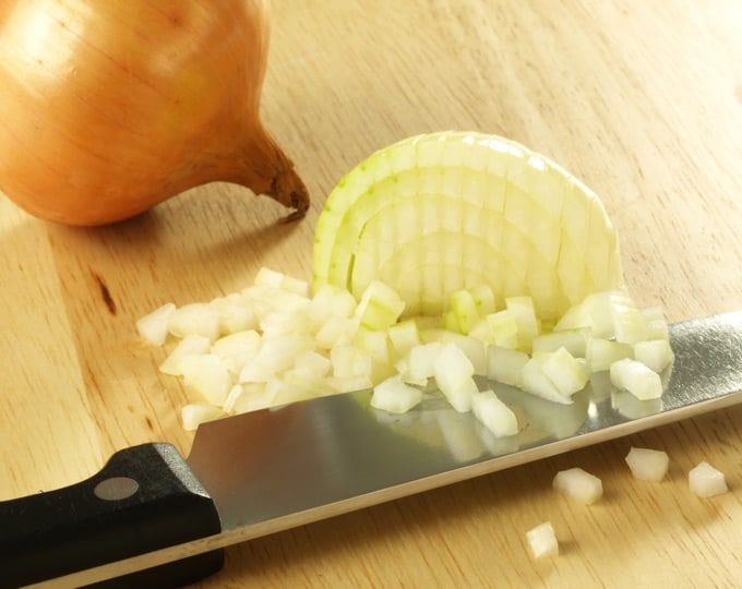 Chopped Onions with knife on cutting board.