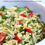 Orzo Pasta Salad with tomatoes, spinach and artichoke hearts in white serving dish