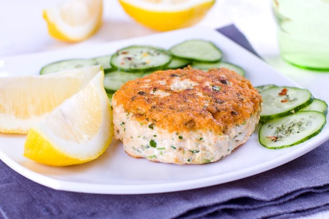 Close up of a salmon cake served with cucumber and lemon
