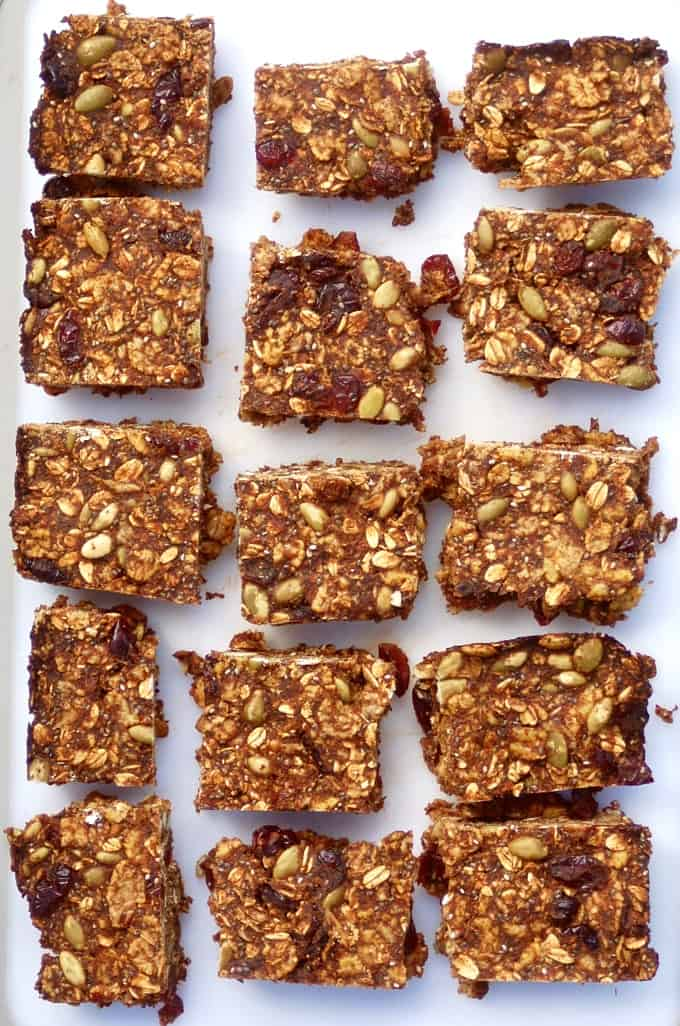 Breakfast bars with oats, pumpkin seeds and dried fruit on white tray.