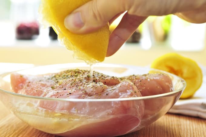 Squeezing fresh lemon juice over raw chicken breasts topped salt and black pepper in glass bowl.
