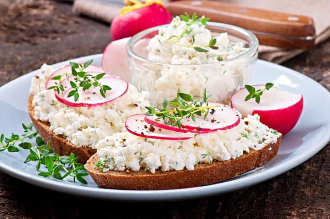 dip of cottage cheese spread on bread with sliced radishes