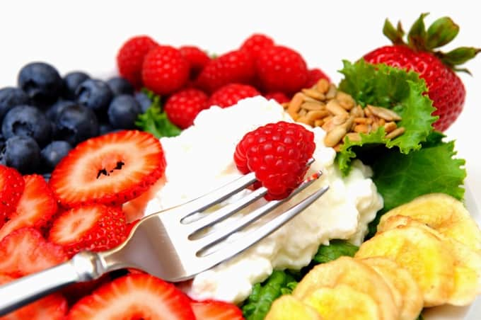 Closeup of a cottage cheese salad with berries including Raspberry, Blueberry, Strawberry and Banana chips