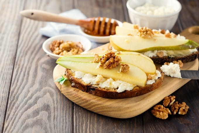 cottage cheese on toast with sliced pears with drizzle of hone and walnuts on a board