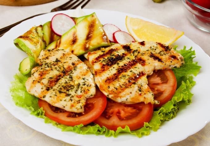 Grilled chicken breasts served with lettuce, tomato and zucchini