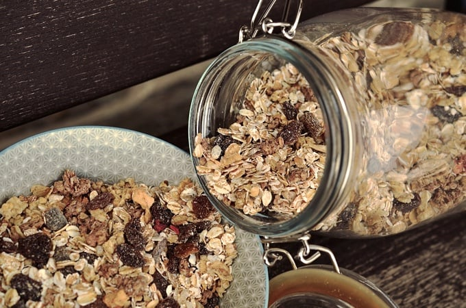 Pouring muesli with dried fruit from sealed glass jar into bowl.
