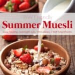 Pouring milk into wooden bowl of muesli with fresh dried fruit and fresh strawberries.