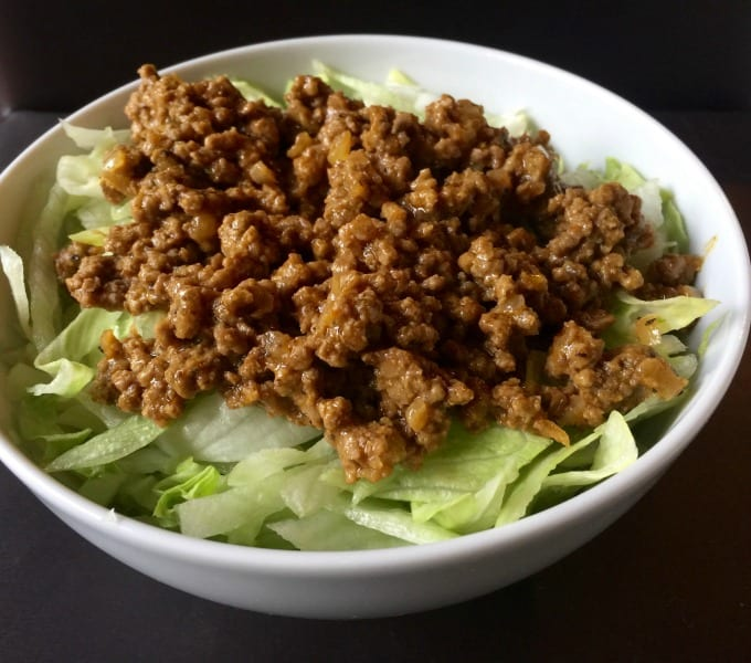 Shredded lettuce topped with crumbled cooked ground beef in white bowl