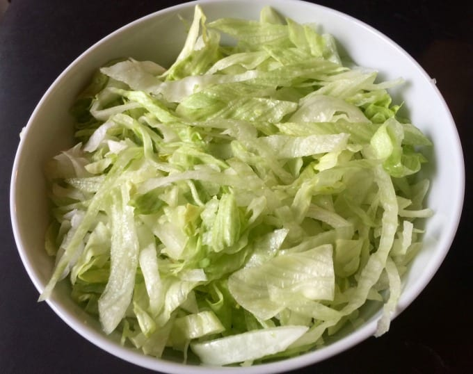 Shredded lettuce in white bowl