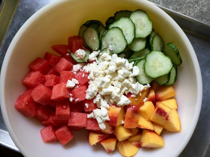 Chunks of Watermelon, Peaches, Sliced Cucumbers and Feta Cheese in a Yellow Bowl from Above