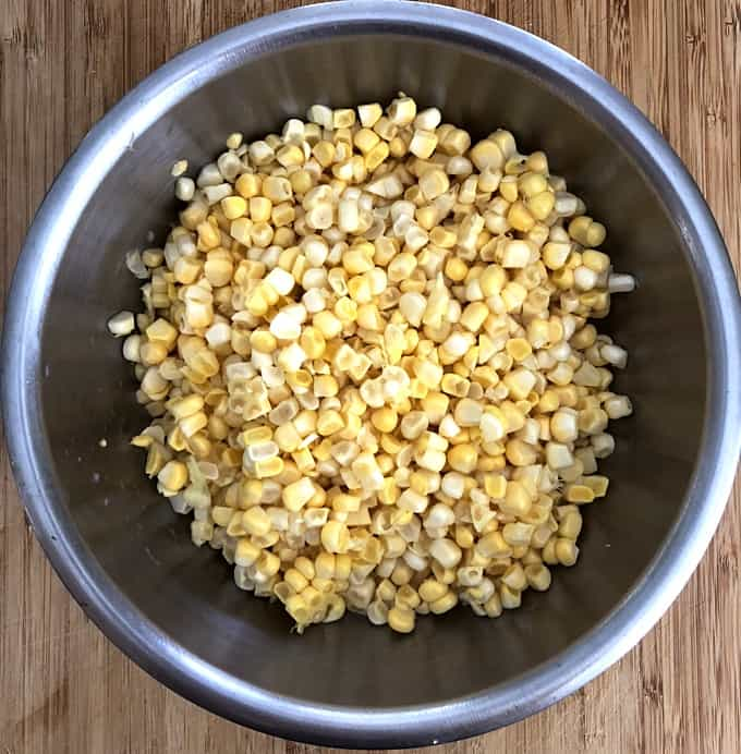 Fresh corn kernels in stainless bowl on wood table.