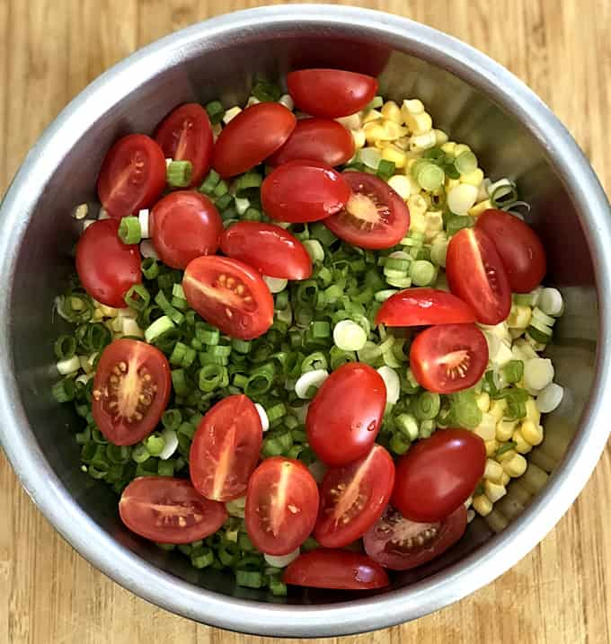 Cherry tomatoes, corn kernels and green onion in stainless bowl on wood table.