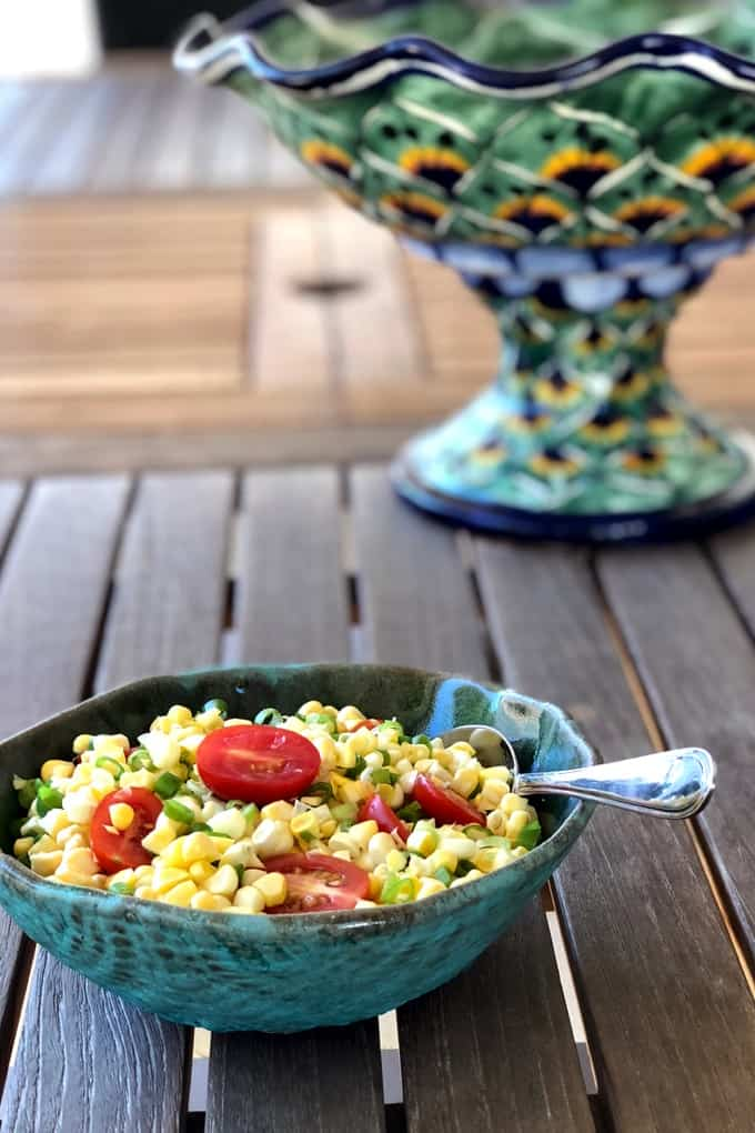 Corn and tomato salad in a green ceramic bowl on a wooden table with talavera pottery in the background