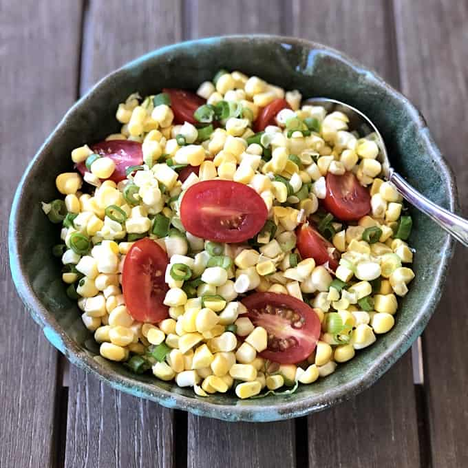 Summer Corn Tomato Salad in green ceramic bowl with spoon on wood table.