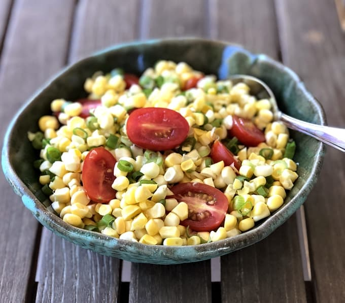 Summer tomato corn salad in green bowl with spoon on wooden table.
