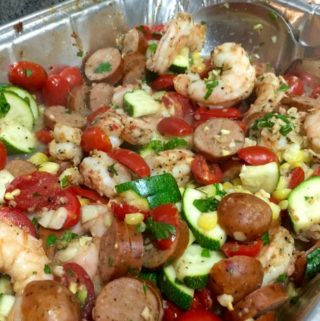 shrimp, sausage, corn, zucchini, tomatoes and spiced in aluminum foil pan