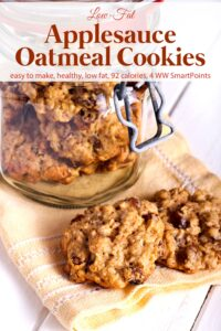 Glass jar with applesauce oatmeal cookies with two cookies sitting on yellow napkin.