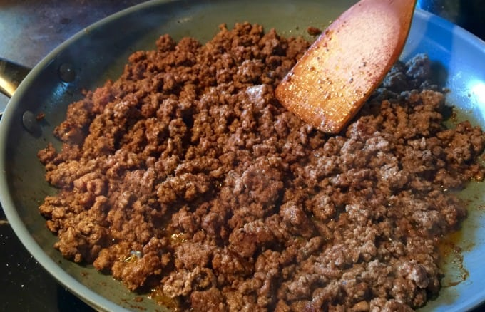 browned ground beef in skillet wooden spoon