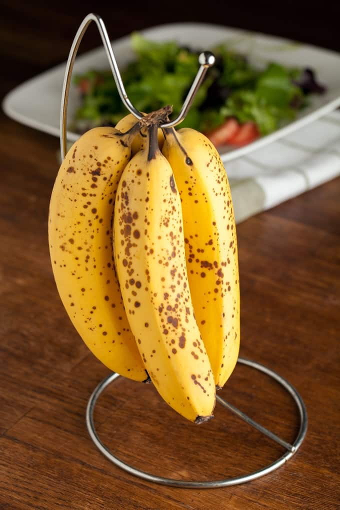 Cheetah spotted bananas that are sweet and ripened hanging on a rack