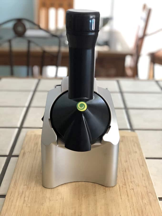 Fully Assembled Yonanas Machine on a wooden cutting board on the kitchen counter