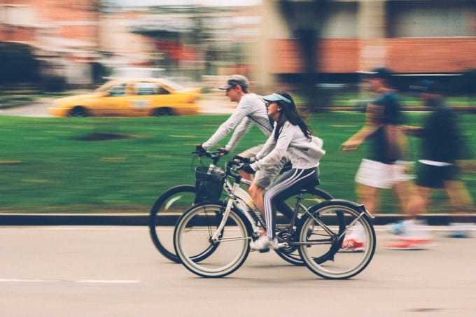 A couple riding bicycles in the city