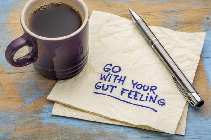 go with your gut feeling - advice or motivational reminder on a napkin with cup of coffee