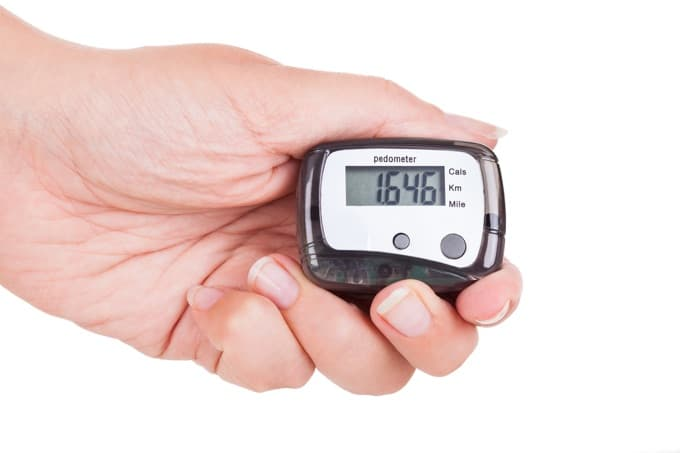 Close-up Of Woman's Hand Holding Digital Pedometer On White Background