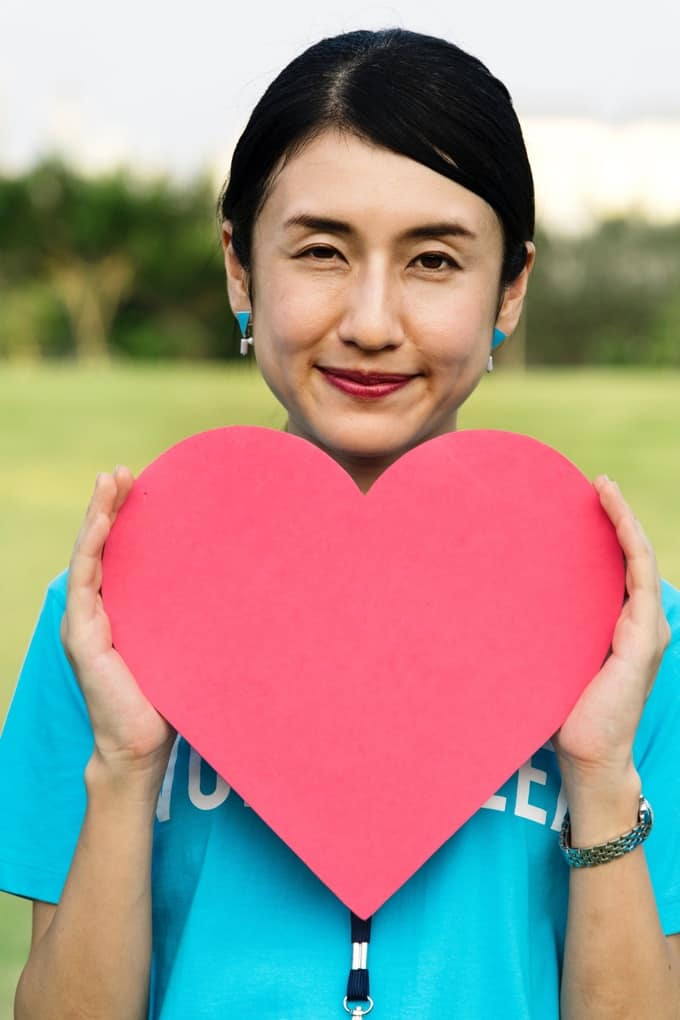 Asian woman holding a red paper heart