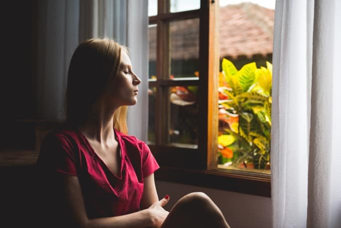 Relaxed woman sitting near open window with eyes closed