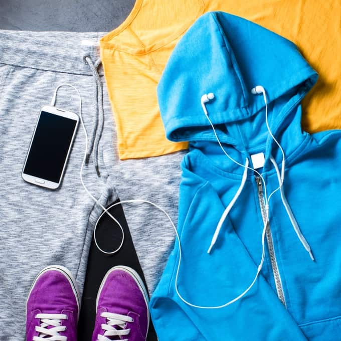 Exercise clothes including gray sweatpants, yellow t-shirt, blue hooded sweatshirt, purple sneakers and iPod with earphones