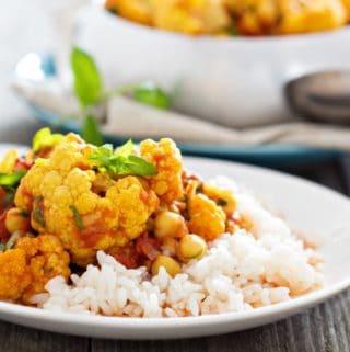 healthy vegan cauliflower curry on rice white plate