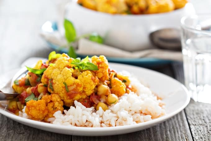 healthy vegan cauliflower curry on rice white plate