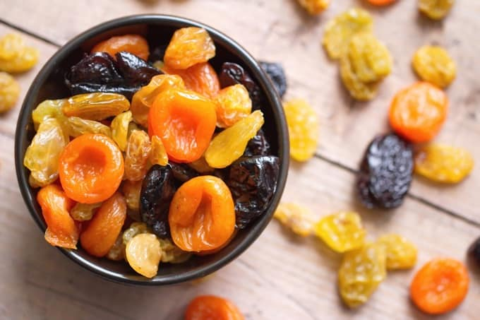 Dried apricots, prunes and golden raisins in a bowl on a wood table