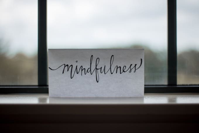 The word Mindfulness written in calligraphy on a piece of paper in a window