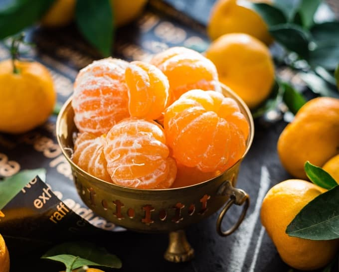 Small copper bowl with peeled clementines and unpeeled clementines scattered around