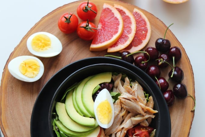 Salad with avocado and chicken next to cherries, grapefruit slices, cherry tomatoes and a hardboiled egg cut in half on a wood cutting board