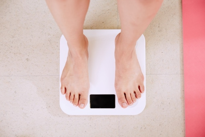 Barefoot woman standing on digital bathroom scale
