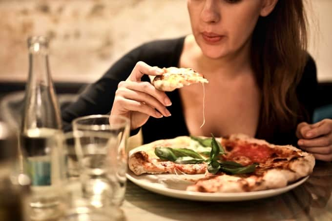 Woman at a table eating pizza