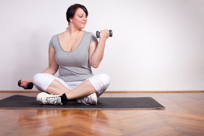 Overweight woman exercising, lifting weights at home
