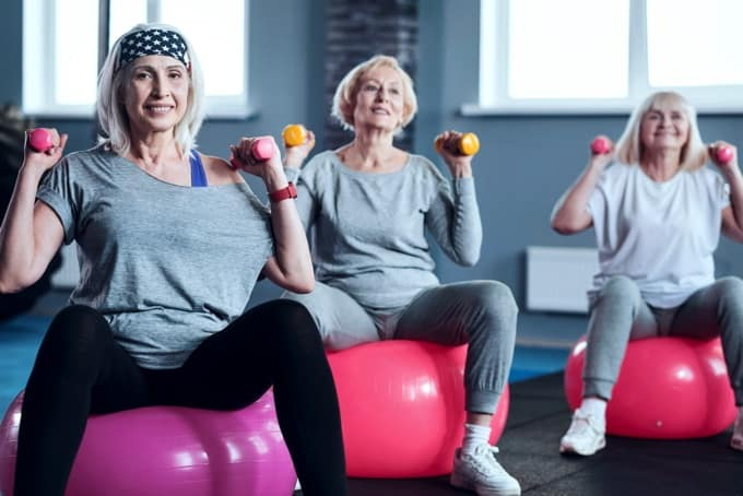Three senior women lifting weights while sitting on balance balls