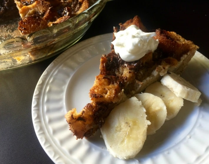 Piece of chocolate banana bread pudding with slices of banana and topped with dollop of whipped cream.