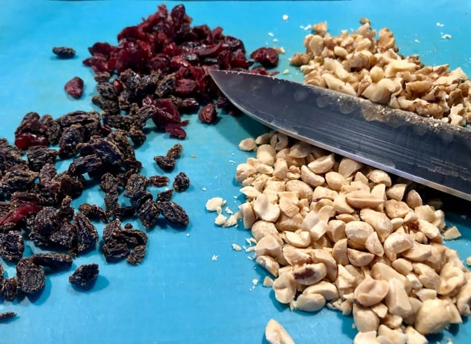 Chopped Raisins, Dried Cranberries and Nuts on a blue cutting board with knife